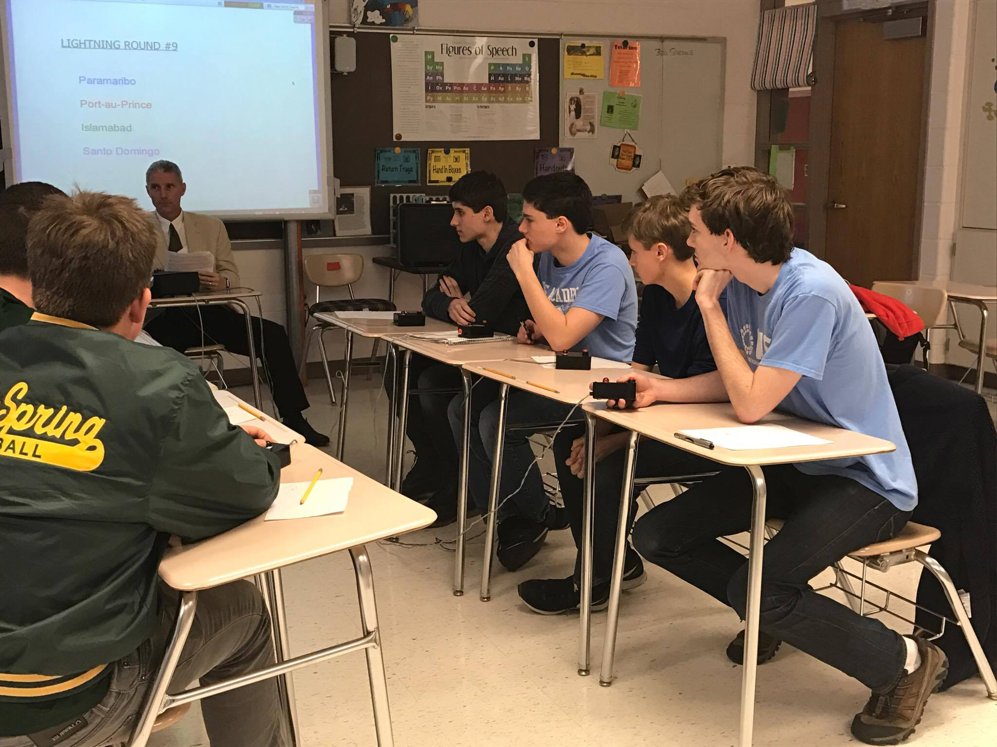Senior Michael Hepburn, senior Ellis London, junior Braden Longstreth, and freshman Nate Olson practice buzzing in to answer questions as they prepare for their final's match Feb. 23 at Blair High School. Photo by Julie Rosenstein.