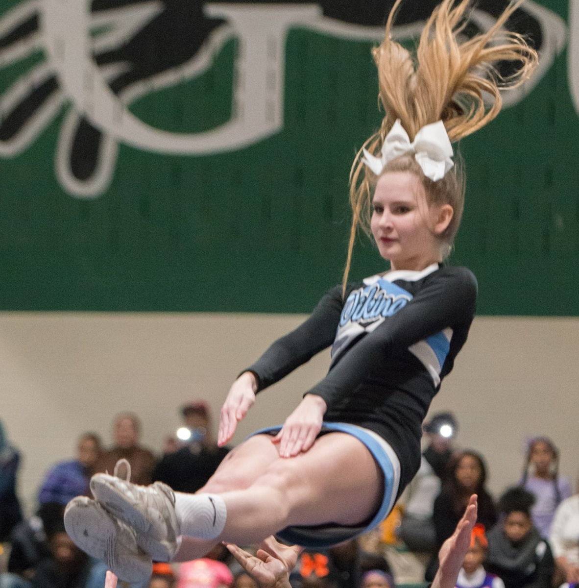 Junior Amanda Erdman soars through the air as the Whitman cheer team caps off their season at the CH Flower's Invitational in Prince George's county. Photo by Jefferson Luo.