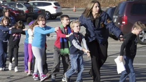 Police lead children from Sandy Hook Elementary School following the shooting Dec. 14. AP Photo/Newtown Bee, Shannon Hicks.