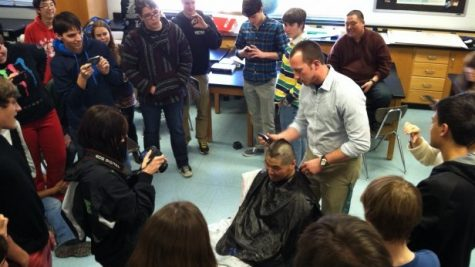 Math teacher Tyler Wilkinson shaves an arrow into physics teacher Daniel Chen's head as students look on. Chen, who is participating in Battle of the Beards, chose to have his head shaved in an attempt to raise more money for the Leukemia & Lymphoma Society. Photo by Eyal Hanfling.