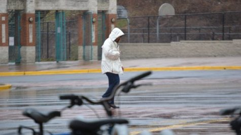 A teacher walks in the rain during the school day today. The torrential downpour let up around 1 p.m. Photo by Abigail Cutler.