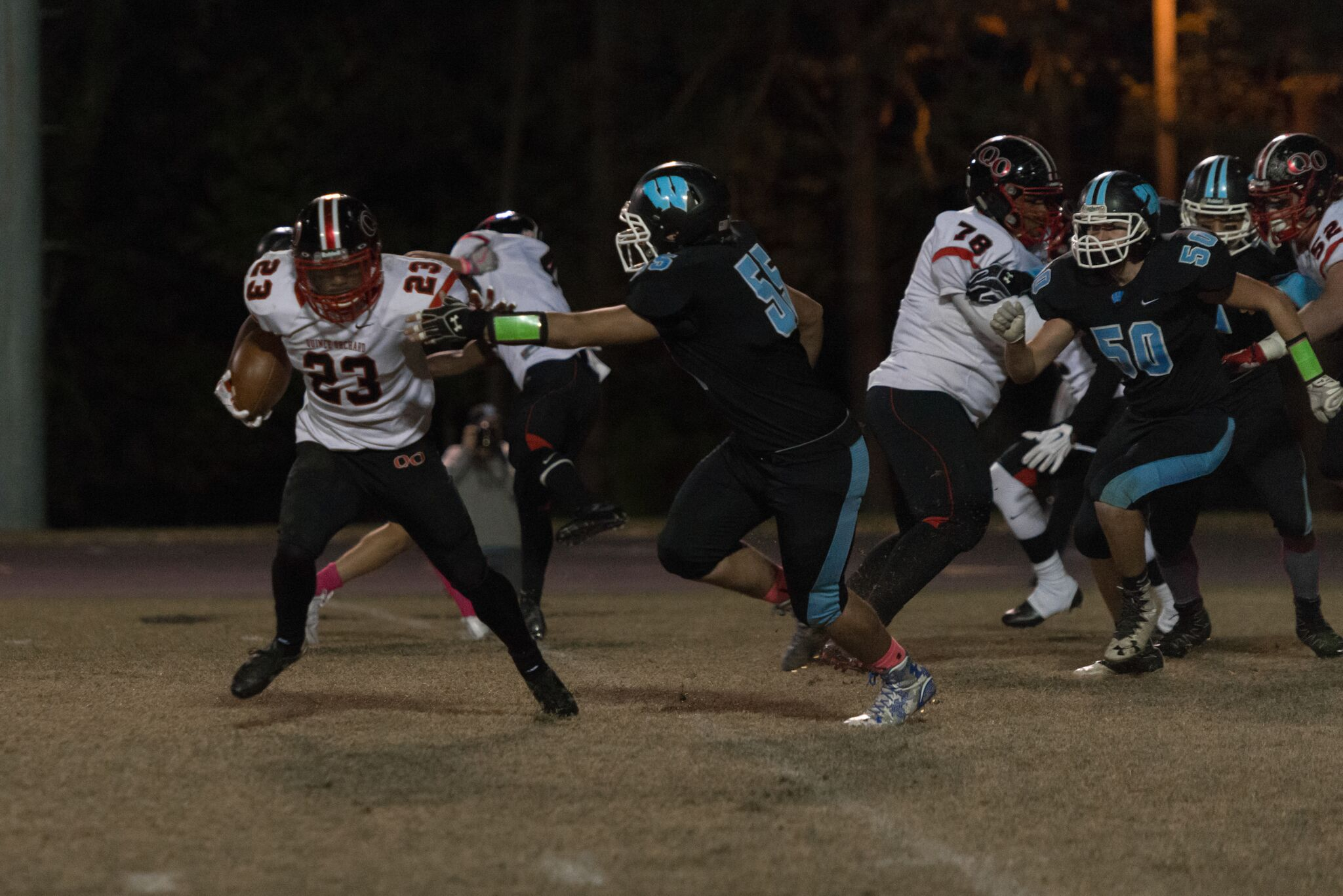 Defensive lineman Dawson Mackay looks to take down QO's running back in the backfield, with linebacker Ben Wilson trailing in pursuit. Photo by Jefferson Luo.