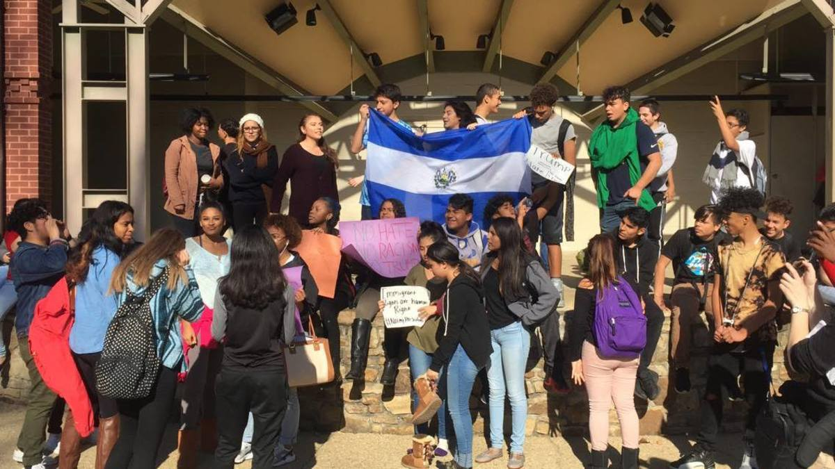Students, many from Watkins Mill and Gaithersburg, wave flags and signs to express support and pride for immigrants and minorities during a walkout protest Nov. 18. Photo courtesy the Current.