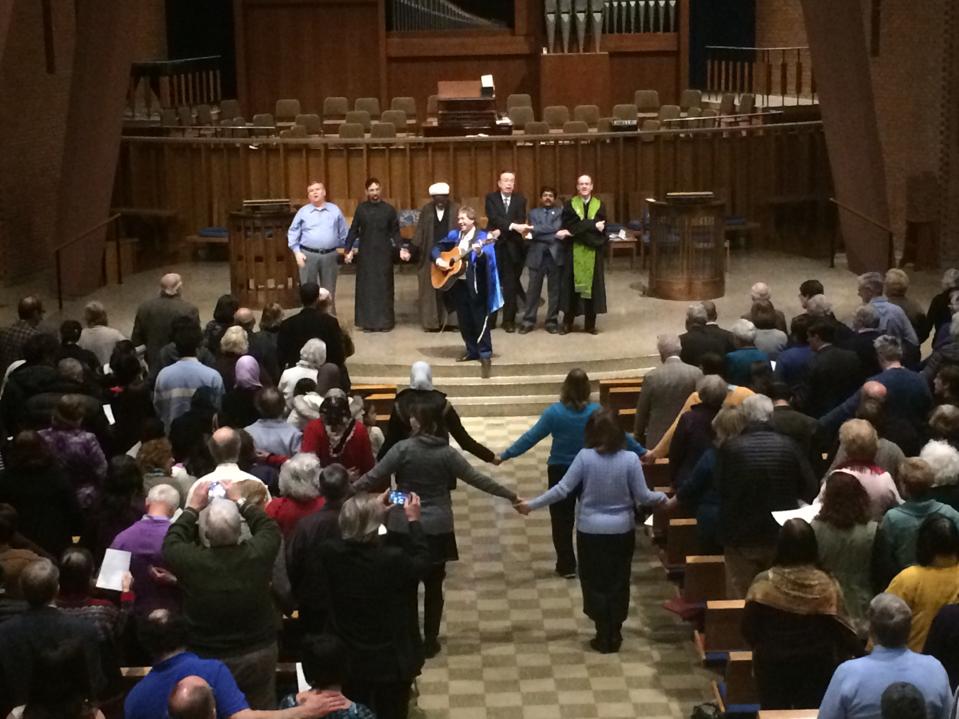 "After a series of prayers Feb. 9, worshippers joined hands and sang ""We Shall Overcome,"" the final anthem of the service held in the shared sanctuary of BHPC and BJC. Photo by Camille Caldera."