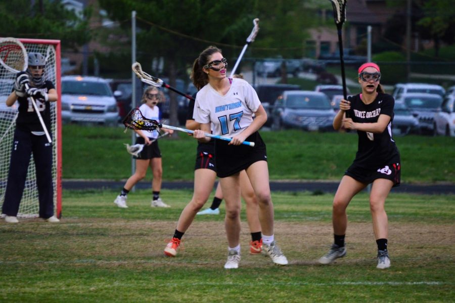 The girls lacrosse team looks to push the ball out of the defensive zone in Thursday's game against QO. Photo by Annabelle Gordon.