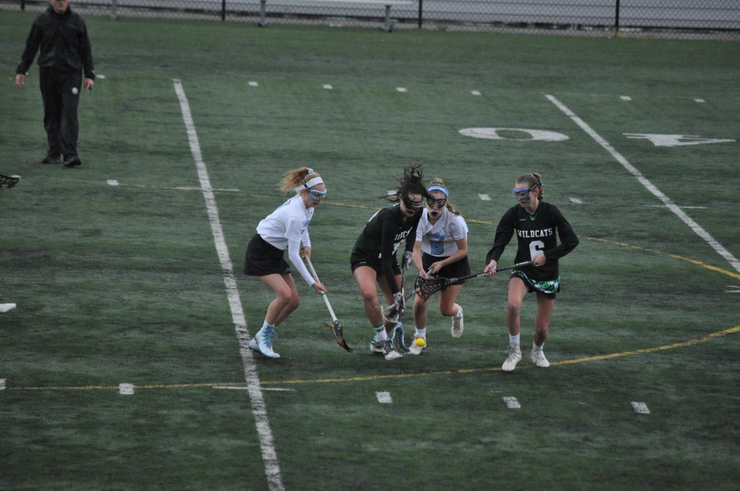 Midfielders Emily Schweitzer and Hanna Freund fight for the ground ball to stop the Wildcats' offensive break. The Vikes eliminated Walter Johnson from the playoffs Friday night. Photo courtesy of Jaiwen Hsu