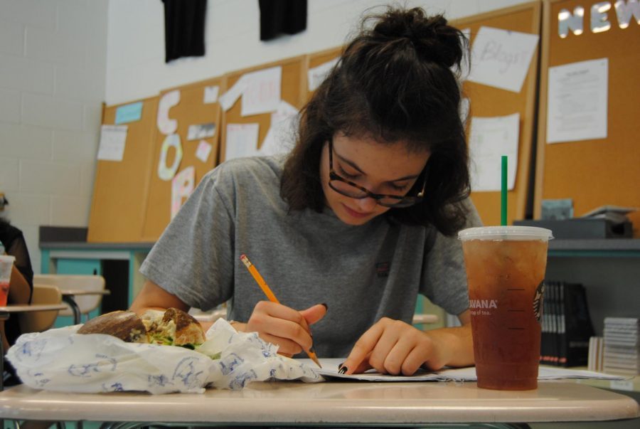 A+student+eats+their+lunch+during+class.+Many+students+are+forced+to+eat+lunch+during+their+classes+because+the+school+only+offers+some+specialized+classes+during+lunch+periods.+Photo+by+Isaac+DeMarchi.+
