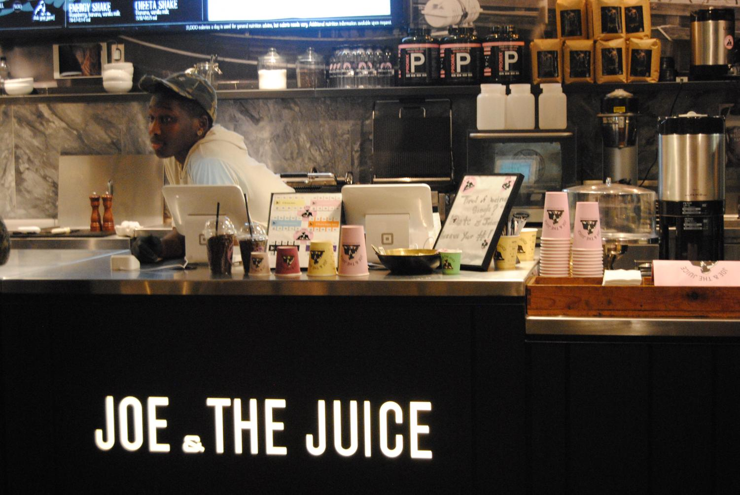 An employee stands behind the counter at Joe & the Juice, a new juice bar in Bethesda. The juice bar serves drinks, but is most well-renowned for its fun customer service. Photo by Isaac DeMarchi.