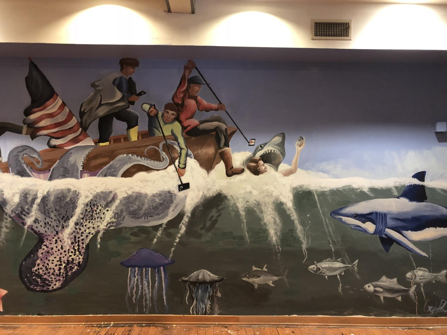 Fish and sharks swarm a wooden raft as an octopus grabs hold of a vessel in a mural in the Museum of Contemporary American Teenagers. B-CC students created the museum after an assignment in their IB Anthropology class. Photo by Rebecca Hirsh.