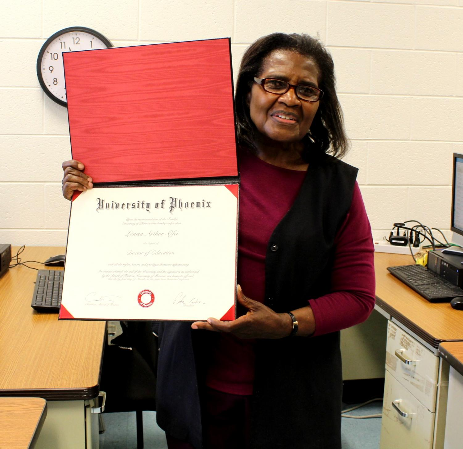 Paraeducator Louisa Arthur holds up her Ph.D. certificate from the University of Pheonix. Arthur earned her doctorate in education after seven years of online classes. Photo by Annabel Redisch.