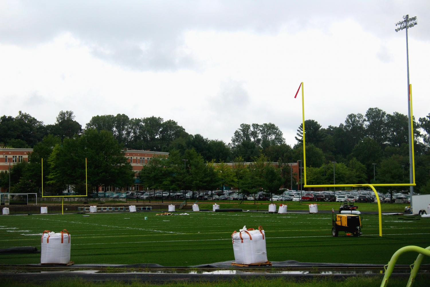 Construction on the turf field pauses for the day due to rain. After four months of work, the field remains unready for use.