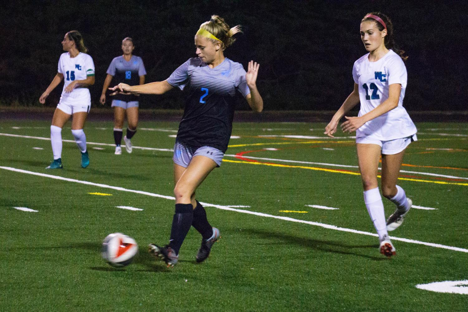 Midfielder Kasey Donaldson plays a pass in girls soccer's Monday night game against Churchill. Girls soccer was one of the first teams to have a home game on the newly finished turf field. Photo by Lukas Gates.