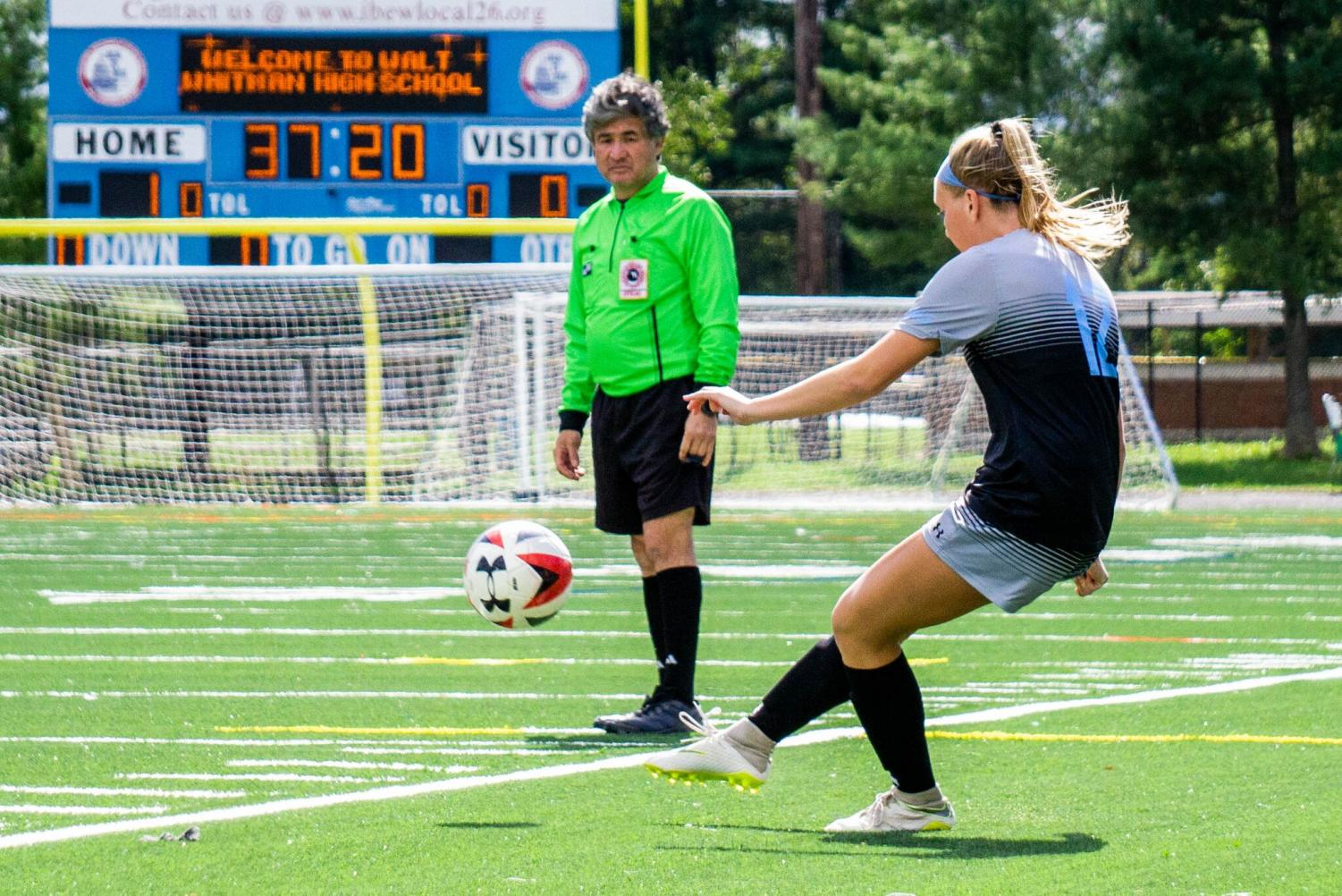 A soccer referee looks on as a Whitman player passes the ball. Recently, the number of high school soccer referees has decreased as a result of verbal abuse.