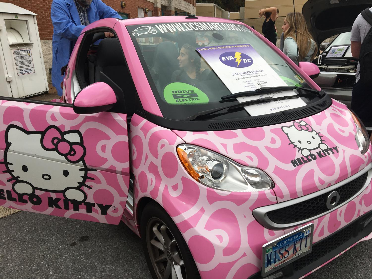 A student sits in EVADC member Wallace Rumbarger's electric car. Rumbarger originally bought the Hello Kitty design for marketing, but now he likes the decor  because it