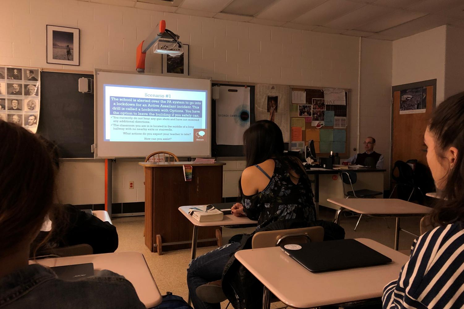 Students look on as English teacher Todd Michaels walks the class through possible scenarios under the new active assailant policy. All teachers gave the same county-provided presentation, and supplemented it with hypotheticals specific to their classrooms.