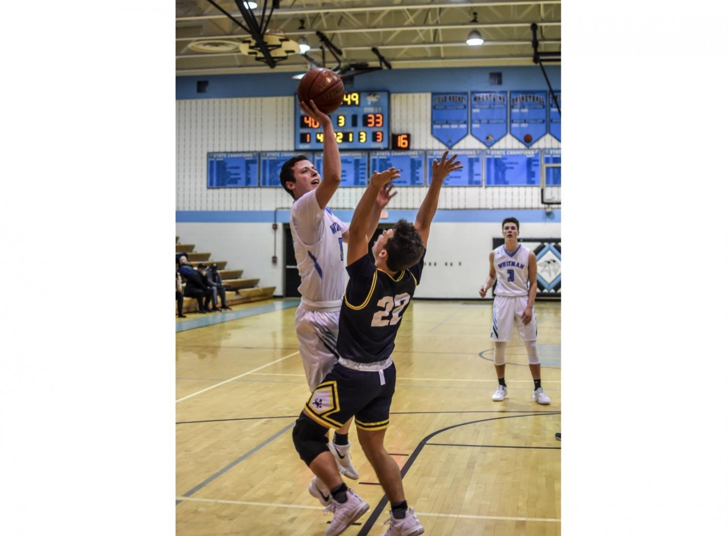 Forward Jason Lewis goes up for a contested layup in the teams 62–61 loss against rival B–CC. Photo by Ryan Gaines.