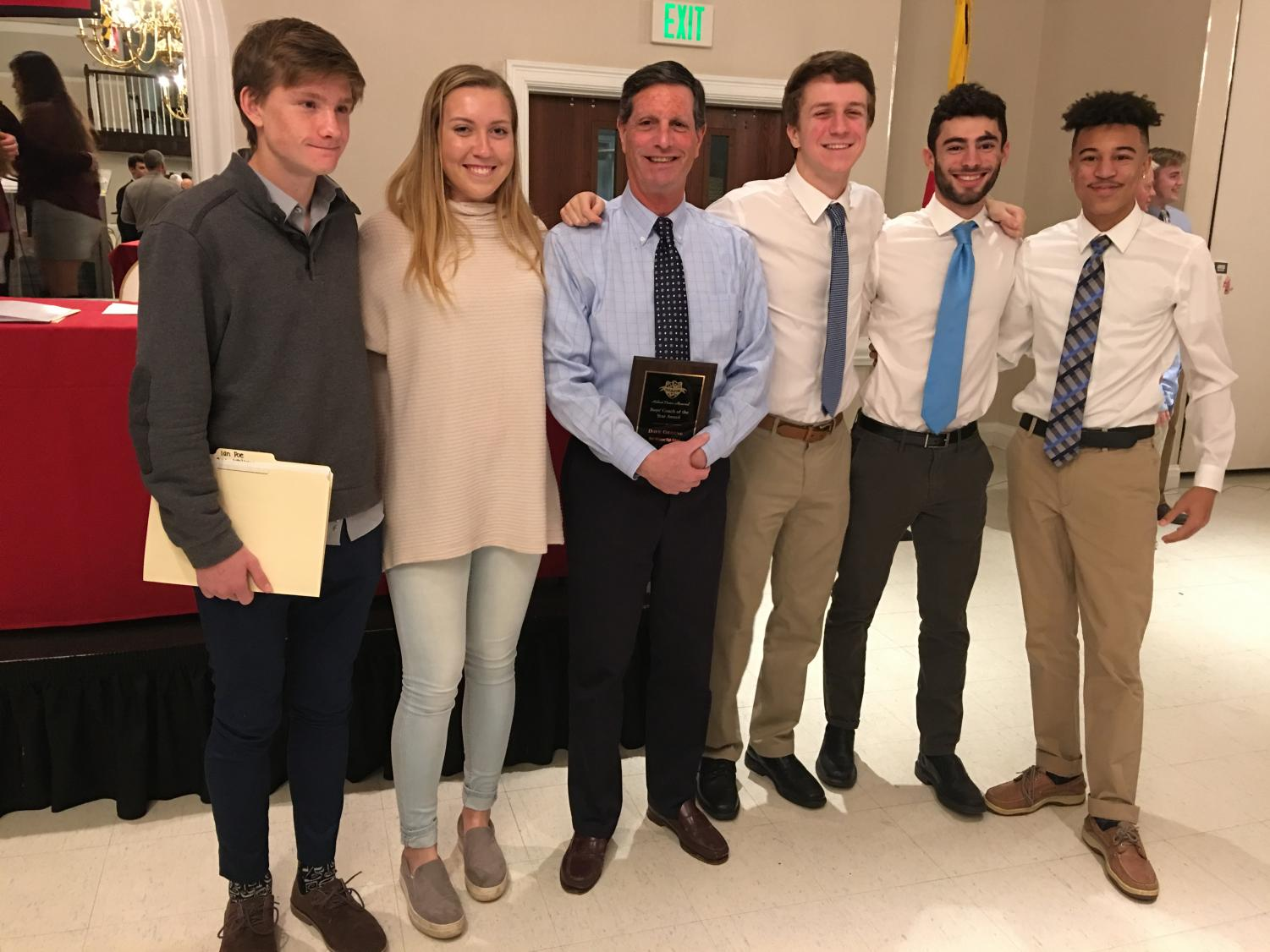 Boys soccer coach Dave Greene takes a picture with four of his players and girls soccer captain Morgan Wiese at the MACS All State Banquet. Greene was honored as the MACS Coach of the Year for the first time in his 40 year career.