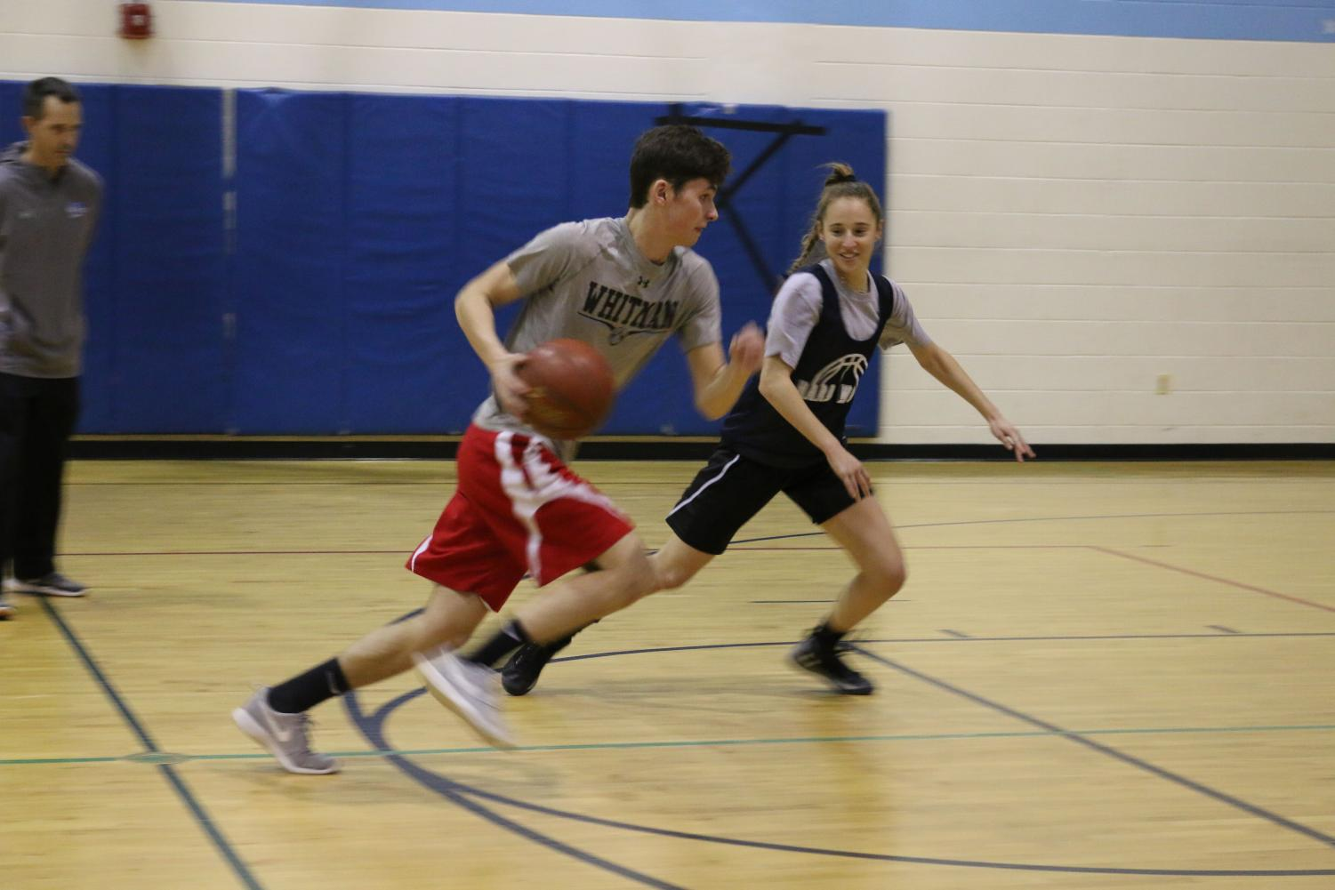 Senior Greg Shaffer dribbles the ball down the court as part of the boys practice squad. The girls team plays against the squad for a tougher physical challenge.