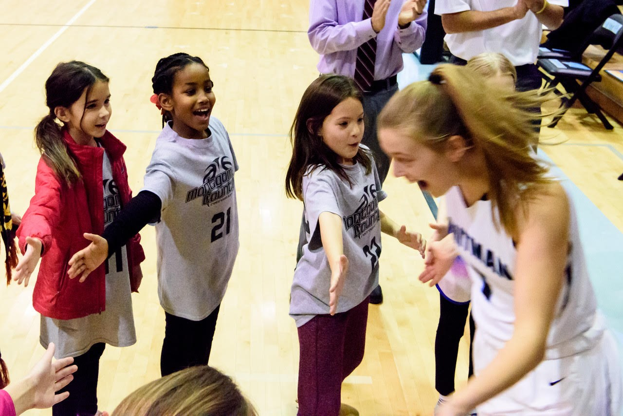 Girls on a Montgomery County recreational basketball team high five Carter Witt ('18) before a game. The Youth Teams program aims to expose recreational basketball teams to high school varsity basketball.