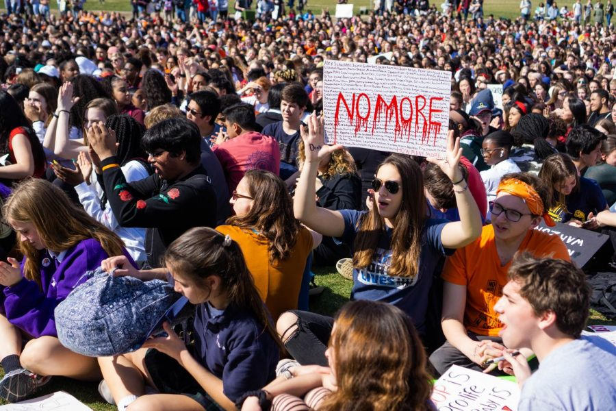 A student holds up a sign—letters written to resemble dripping blood—in a crowd.  This was the second student walkout for gun control after the Parkland shooting last year.