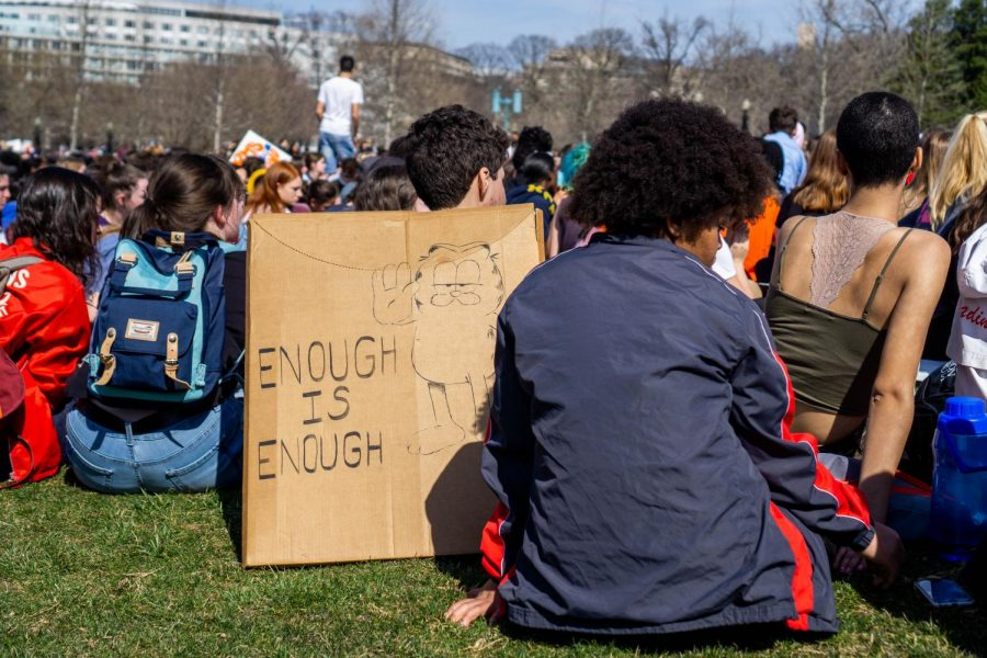 A student sits by his sign in respect of 17 minutes of silence. Each minute represented one victim of the Parkland shooting.