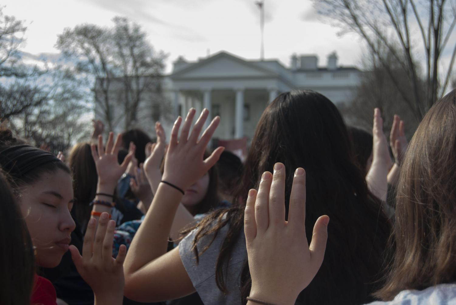 Students hold their hands up to indicate,