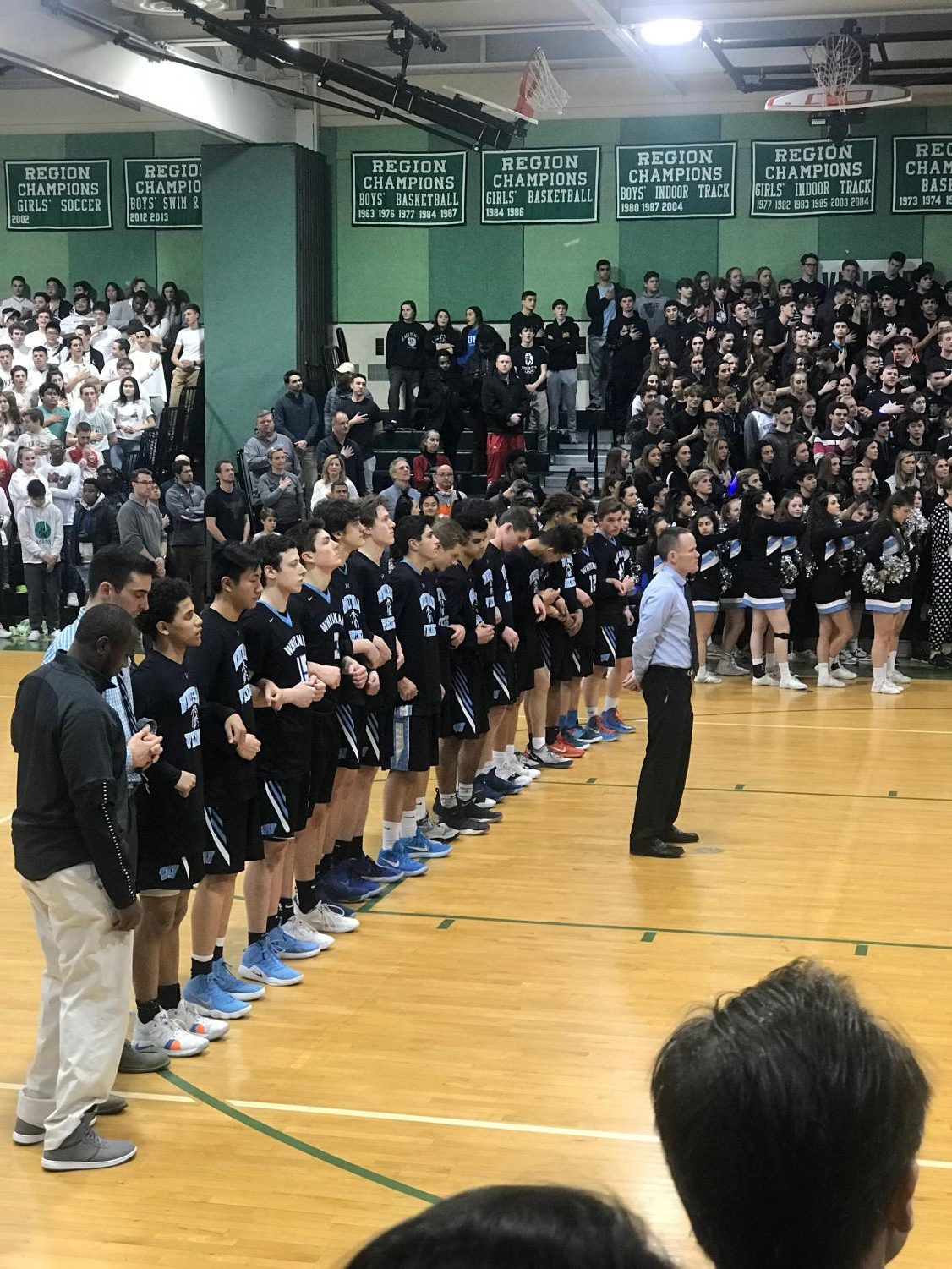 The boys basketball team lines up for the national anthem before the team's playoff loss against the Walter Johnson Wildcats. The team ended their season in a heartbreaking overtime loss, but the players are proud of what they accomplished this season. Photo courtesy Blake Layman.
