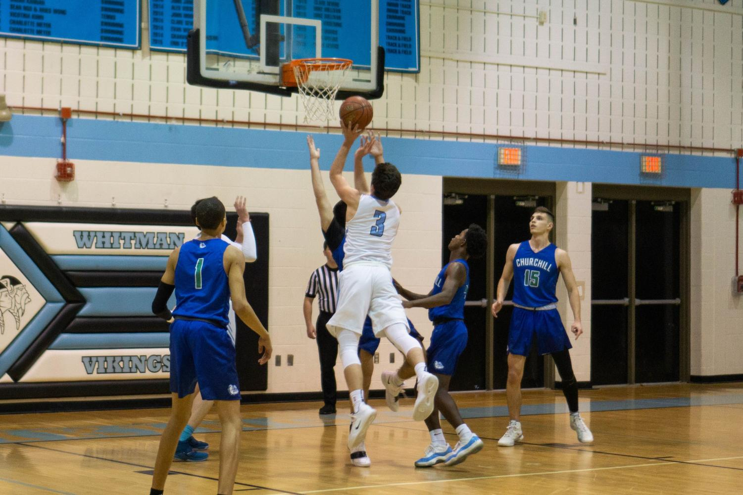 Senior Brendan Shaver drives for a layup against Churchill. The Vikes won both of their regular season games against the Bulldogs by double digits, and will face off with Churchill in the second round of playoffs tomorrow.