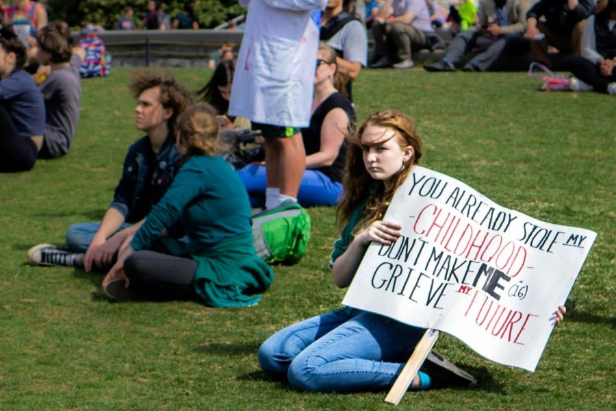A+student+sits+on+the+Capitol+lawn+during+the+March+15+climate+change+walkout.+Students+around+the+world+walked+out+of+class+to+demand+action+on+the+issue.