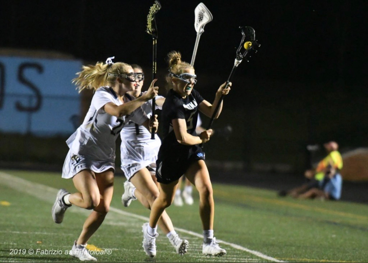 Midfielder Faith Parker runs past two Severna Park defenders in the girls lacrosse team's loss in the state semi-finals to Severna Park. Photo courtesy of Phil Fabrizio.