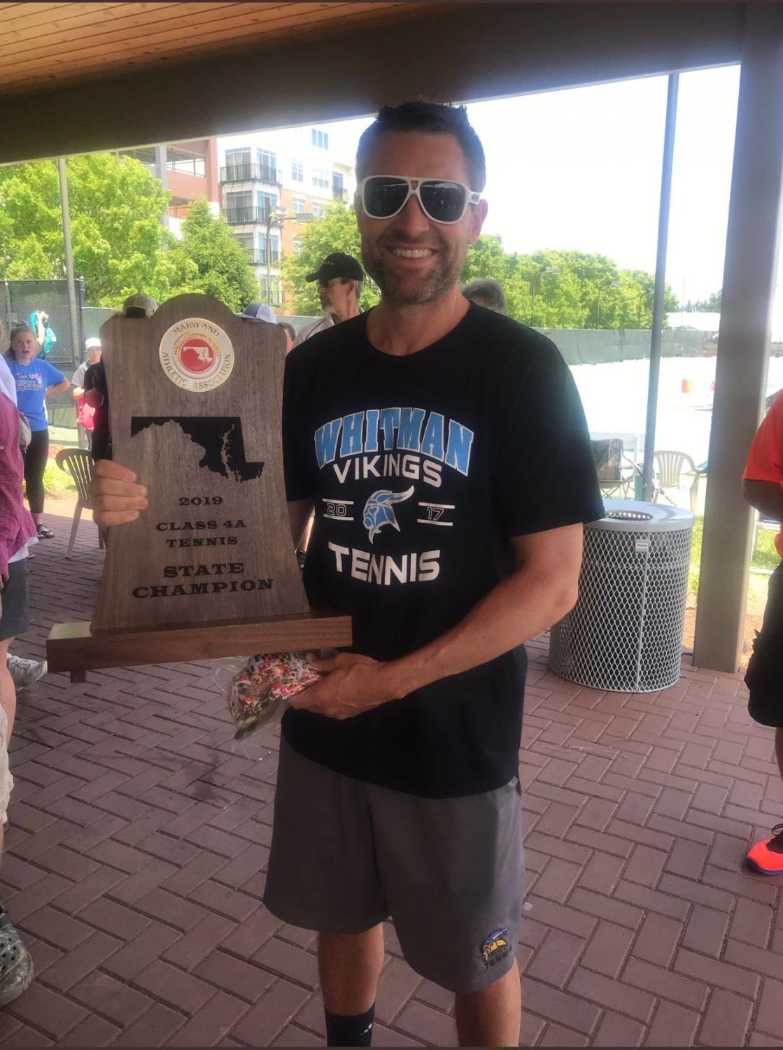Boys tennis coach Jasen Gohn poses with the boys and girls state tennis trophy. Photo courtesy of Jeff Sullivan Twitter.