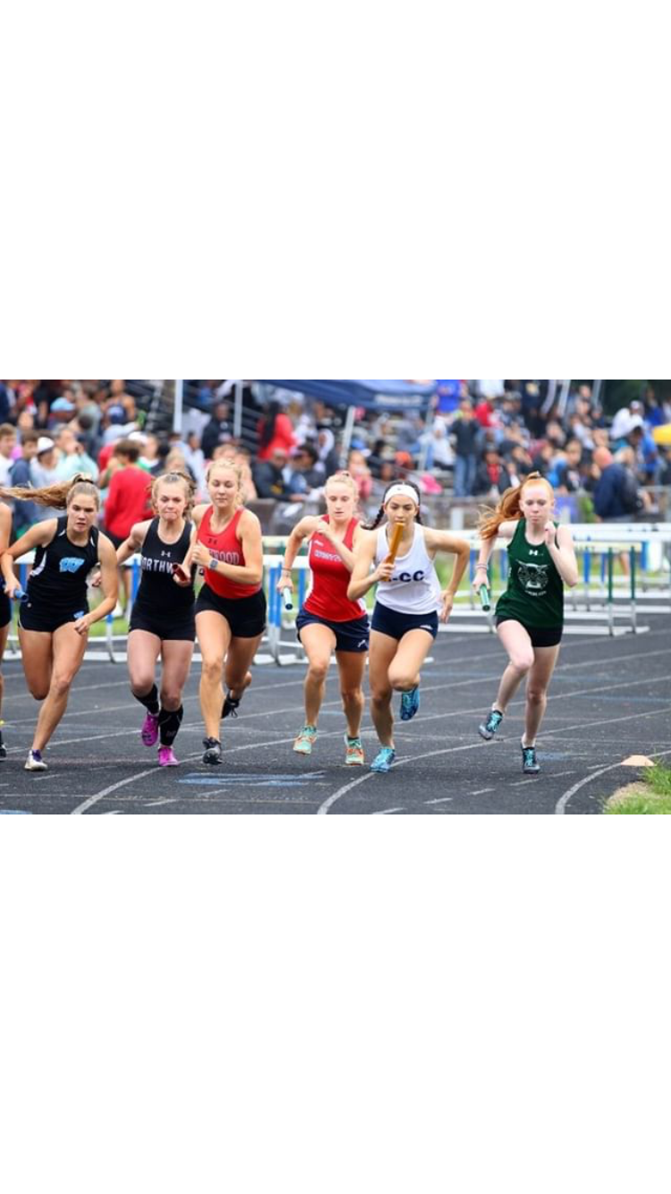 Junior Isabella Bravo (far left) competes in the relay event at the MCPS Track and Field County Championships. Photo courtesy of Elizabeth Sklaire.