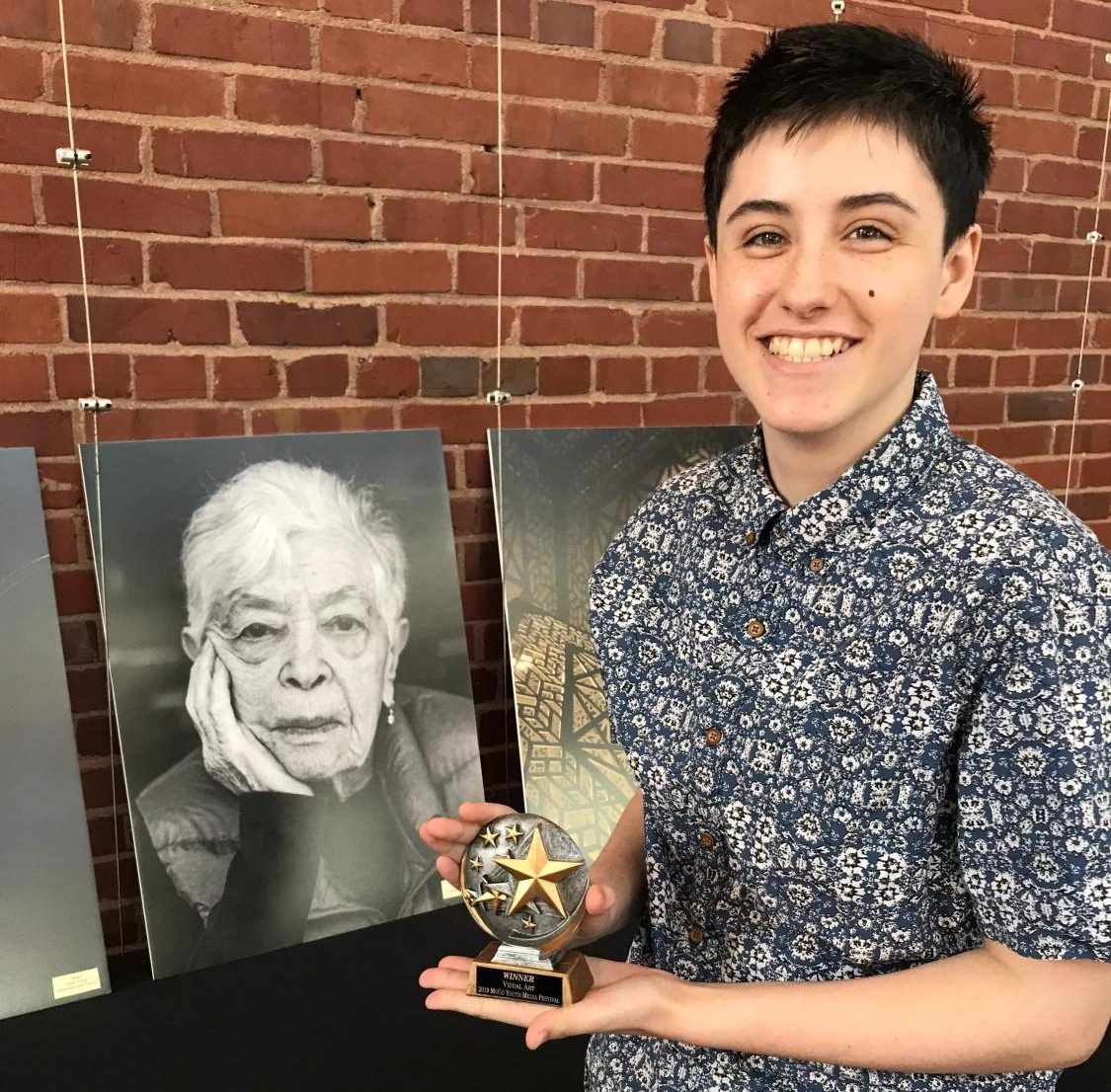 Gates holds his award as he poses next to his photo of Holocaust survivor Ruth Cohen. Gates won $100 for the picture and chose to give Cohen the final photo. Photo courtesy Lukas Gates.
