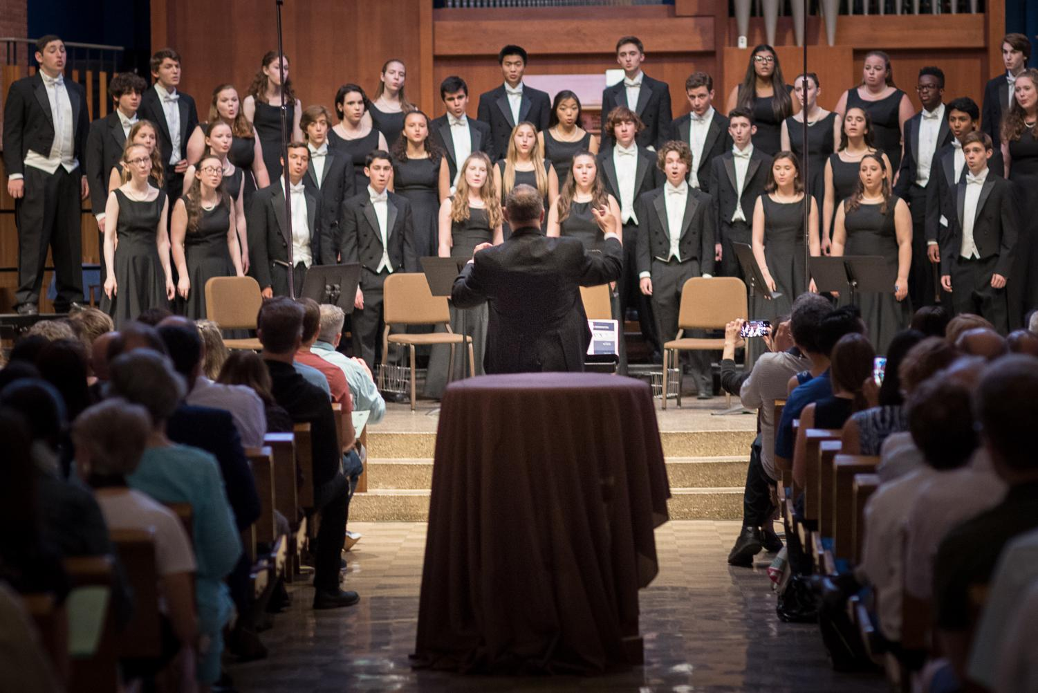 Choral director Jeff Davidson conducts the Chamber Choir as they sing at their annual farewell concert. Davidson will retire this year after 34 years of teaching at Whitman.