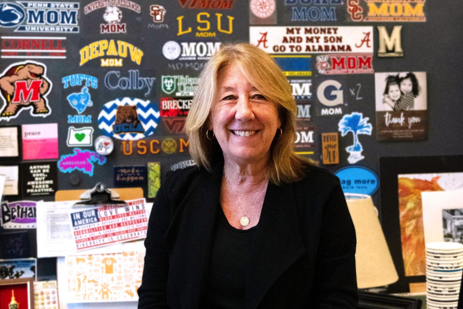Art teacher Nancy Mornini poses in front of her sticker wall. Mornini will retire this year after 20 years of teaching at Whitman.