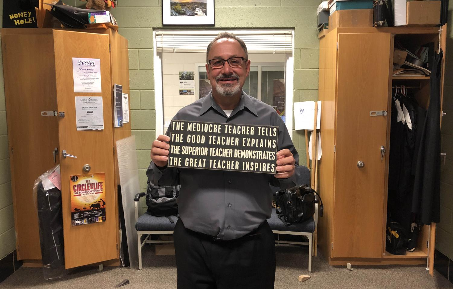 Chorus teacher Jeff Davidson holds up a sign he considers his inspiration for teaching. Davidson's relationship with his students is like that of an