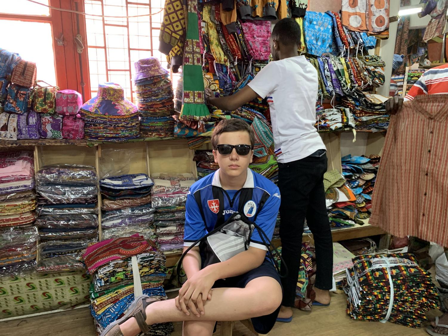Jacopo+Villani%2C+the+younger+brother+of+Where+We+Live+sector+editor+David+Villani%2C+sits+in+a+workshop+at+the+March%C3%A9+Sandaga+in+downtown+Dakar%2C+Senegal.+This+busy+marketplace+is+known+throughout+Senegal+for+its+elaborate+fabrics+and+for+the+high+quality+of+the+artisans+who+work+here.+Jacopo+sports+%244+basketball+shorts%2C+hand-me-down+sandals%2C+a+jersey+from+his+hometown+soccer+team%2C+and+sunglasses+stolen+from+his+brother.++Steal+his+look%E2%80%94if+you+dare.