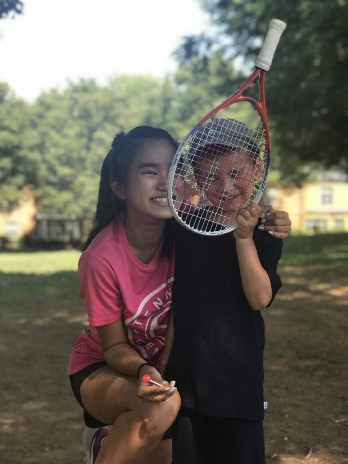 Online+Copy+Editor+Hirari+Sato+smiles+with+four+year+old+Richard+Stark+as+he+covers+his+face+with+his+baby+tennis+racket+at+the+Landon+Tennis+camp.+Sato+coached+three+to+five+year+olds+the+basics+of+tennis+such+as+forehands%2C+backhands+and+volleys+for+nine+weeks.