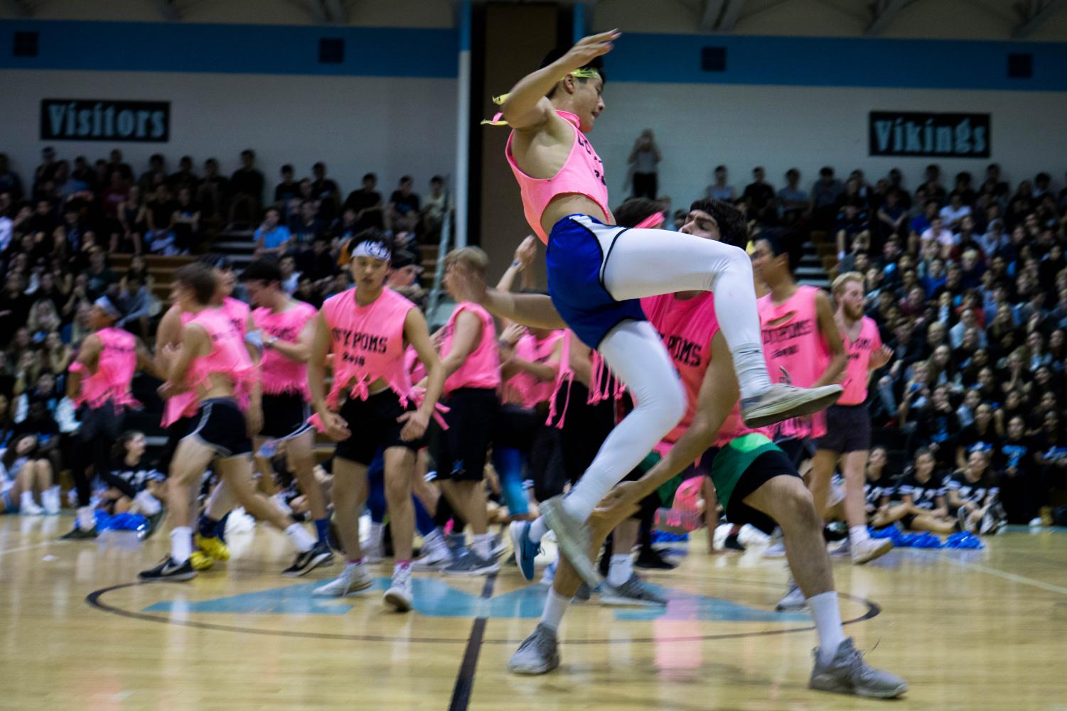 The Guy Poms perform in the main gym at last year's homecoming pep rally. This year, they will perform on the field because the event has been moved to the stadium.
