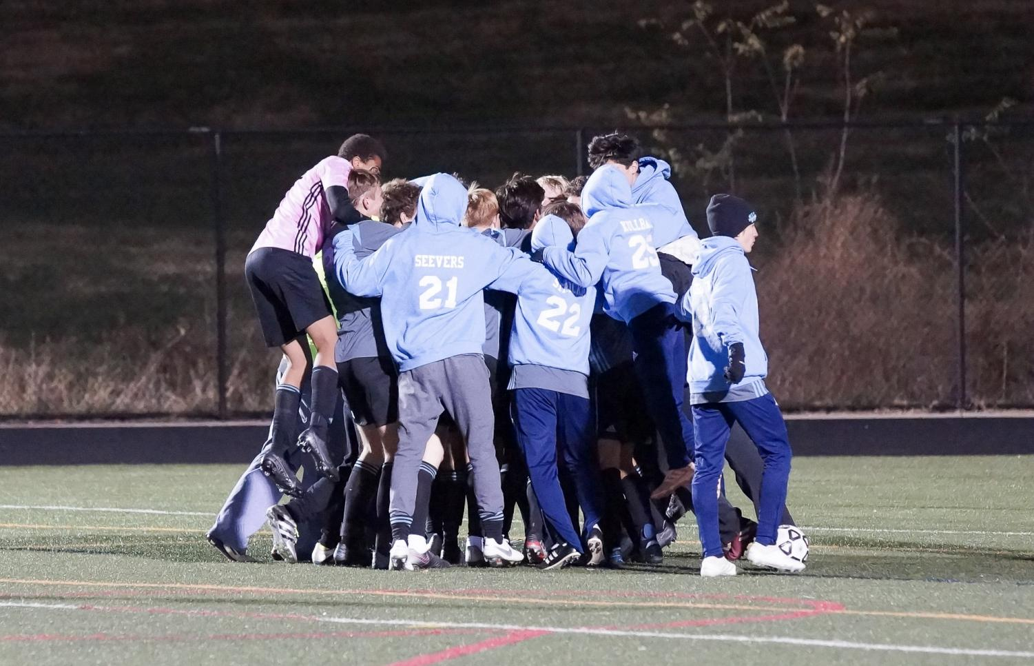 The boys soccer team celebrates their 4–3 overtime win over Wootton in the state semifinals.  Photo courtesy of Sos Mboijana.
