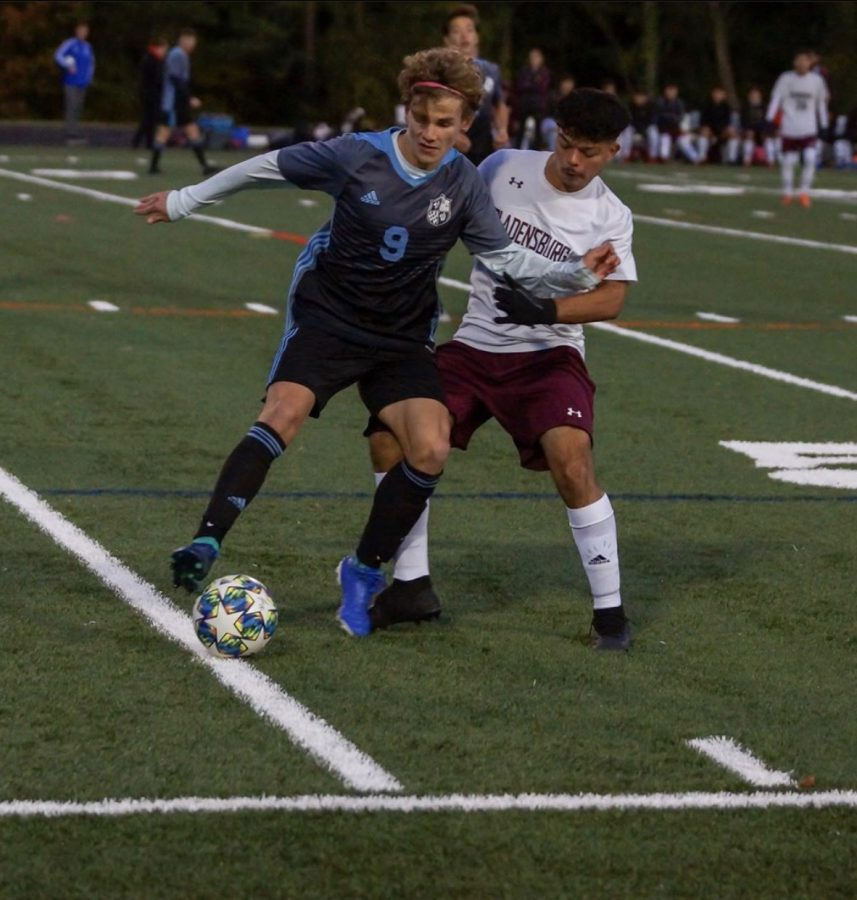 Winger Hugo Barnes holds off a defender in the teams 5–0 win over Bladensburg in the state quarterfinals. Photo courtesy of the Whitman Mens Varsity Soccer Instagram.