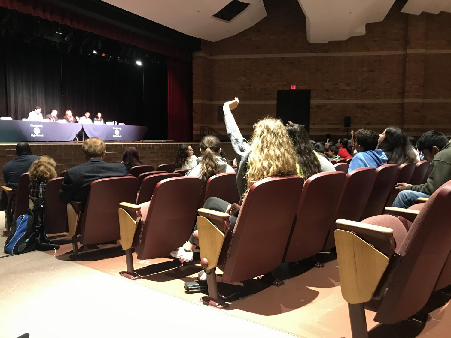 Clarksburg Junior Charlotte Sanford raises her hand to ask the panel a question. She, like many other students at the town hall, asked about how the boundary study would affect her school.