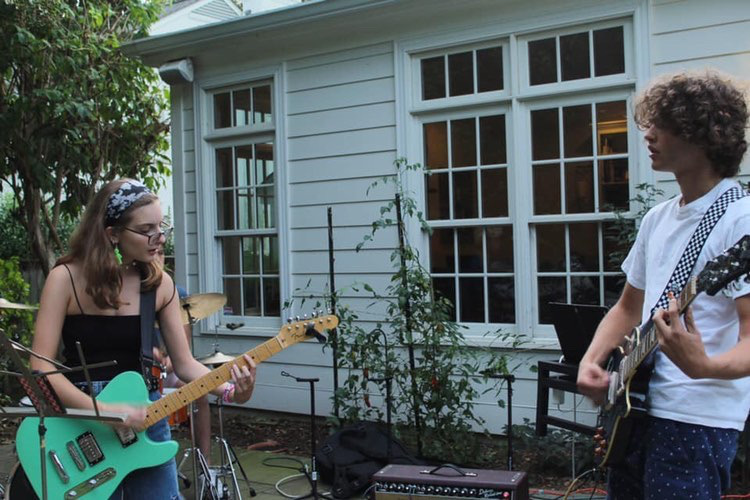Junior Jane Pampillonia performs with senior Renz Johnson at a backyard Coffee House.