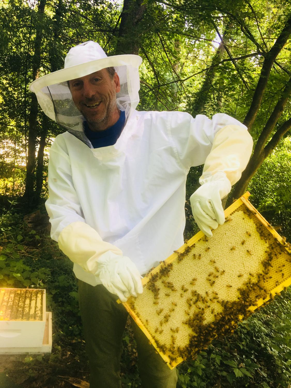 Whitman parent Dan Stoner holds up a tray from his beehive. Each tray holds wax honeycomb that bees fill with honey each spring.