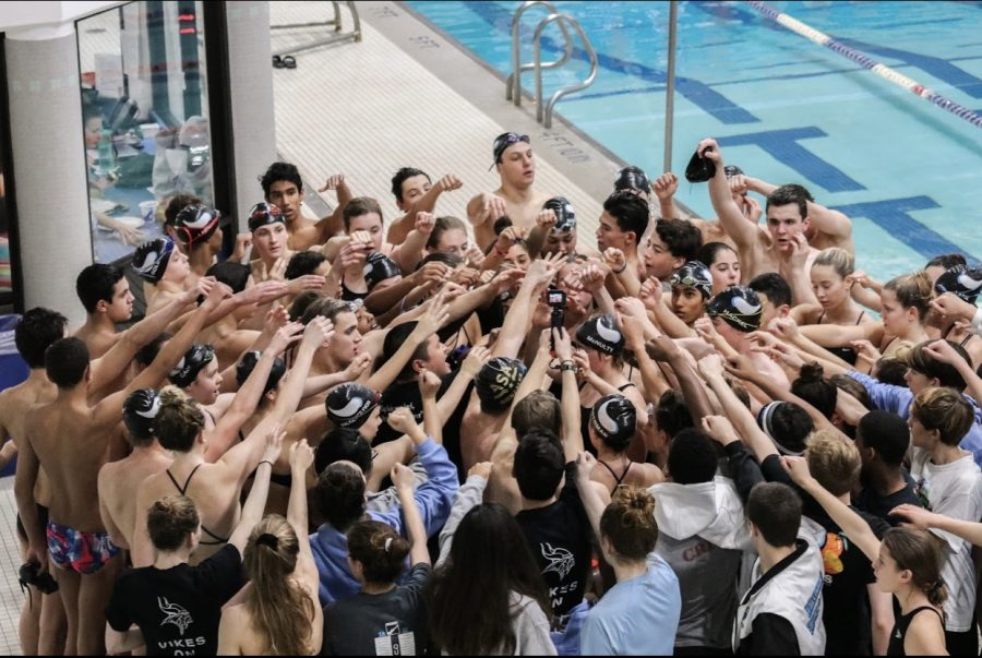 The Swim and Dive team huddle up before their 252–118 victory over the Sherwood Warriors.