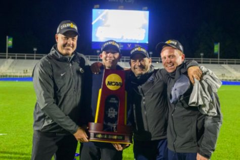 (From left) Georgetown Men's Soccer coach Brian Wiese celebrates winning the NCAA championship by holding the championship trophy.