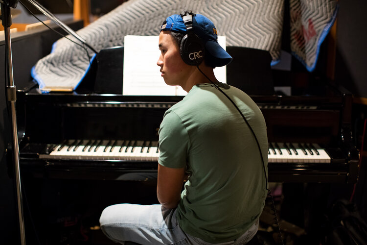 "Bryan Eng ('16) sits at a piano as he plans his arrangements for his album ""20."" Eng attributes Whitman Drama for inspiring him to create his professionally produced, jazzy album."