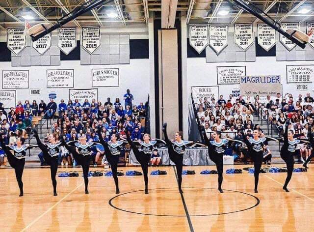 Poms spreads out into a kick line near the end of their six minute routine in their county competition. Photo courtesy of Julia Clayton.