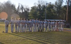 The baseball team looks out into right field while standing for the national anthem.