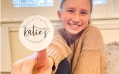 Junior Katie Sklaire holds up a Made by Katie S logo sticker that she decaled using Cricut.